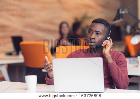 Customer Service agent in an startup office with laptop.