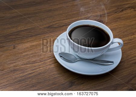 White cup of coffee on vintage wood. Top view cup on wooden table. View from top break or breakfast