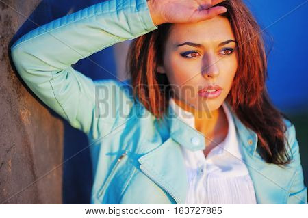 Portrait of young pretty pensive woman with brown hair putting his hand on his head the bright rays of the setting sun close up.