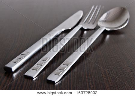 Canteens stainless steel cutlery on dark wooden surface