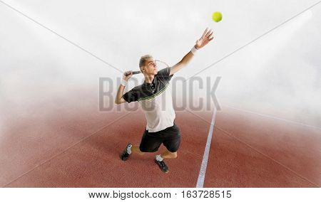 young man play tennis outdoor on orange tennis court at early morning in a fog