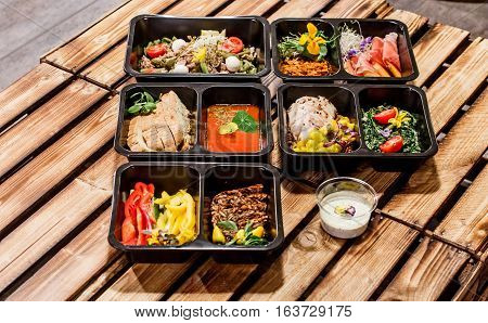 Healthy food and diet concept, restaurant dish delivery. Take away of fitness meal. Weight loss nutrition in foil boxes. Steamed veal with cous and vegetables at wood