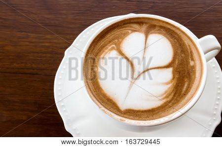 Closeup cup of hot coffee tulip latte art on wood table