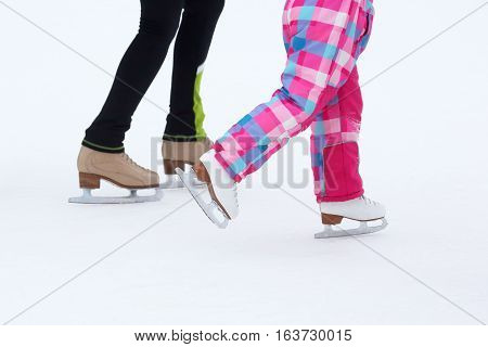 foot skating little girls and women on an ice rink