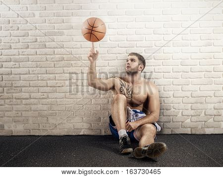 basketball player with ball on the asphalt near the wall with ball and light
