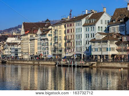 Zurich, Switzerland - 1 January, 2017: historic buildings along the Limmat river, people on the embankment of the river, Christmas illumination lamps temporarily installed along it for the Christmastime. Zurich is the largest city in Switzerland.