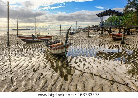 Fisherman boats in Tanjung Aru jetty,Labuan island,Malaysia fishing village with blue sky and clouds at low tide.