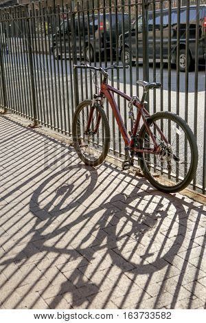 Bicycle chained to a fence with strong shadow