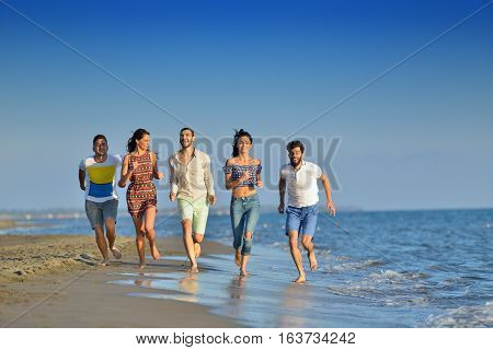 happy young people group have fun white running and jumping on beacz at sunset time.