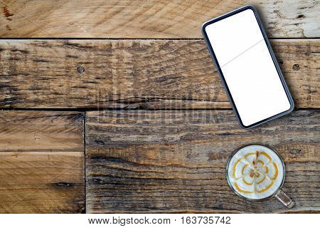 Smart phone with coffee late on wooden.