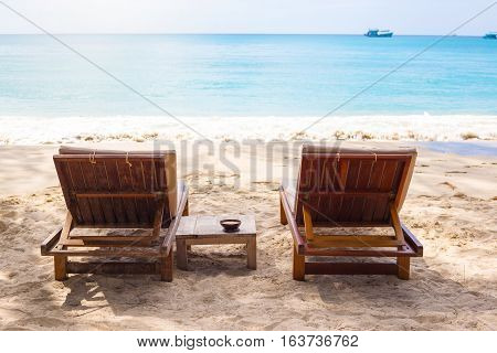 Beach chairs on the white sand beach with blue sky and sun