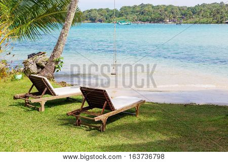 Beach chairs on the white sand beach with blue sky and sun