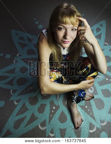 Young blond woman sitting on a painted floor