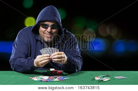 Poker player peeking at cards. Player is wearing a hoodie and dark glasses. Background has blurred lights