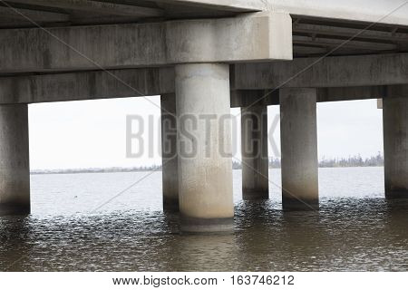 Pillars of overpass bridge over choppy water