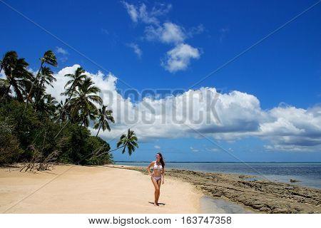 Young woman in bikini standing on the beach of Makaha'a island near Tongatapu island in Tonga. Kindom of Tonga is an archipelago comprised of 169 islands