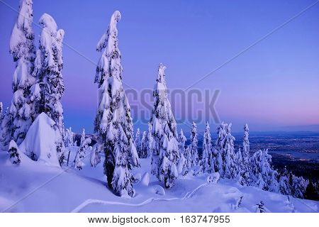 Winter sunset on mountains over city. Hollyburn Mountain. Cypress Provincial Park. North Vancouver. British Columbia. Canada.