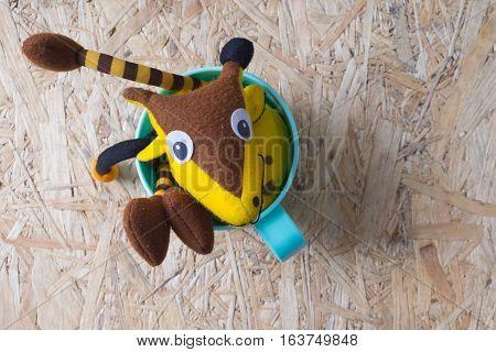Cute Giraffee soft toy in green plastic on wood background