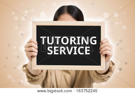 Tutoring Service Text On Chalkboard In Child Hands.