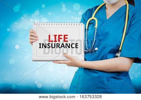 Doctor Shows Life Insurance Text On White Line Paper Book.