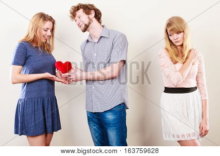 Jealousy and betrayal concept. Abandoned unloved girl watching on happy hugging couple. Triangle relationship.
