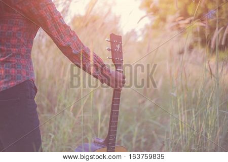 Woman and guitar with grass, happy sunset silhouette