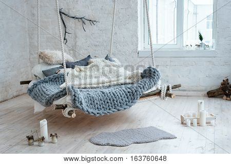 White loft interior in classic scandinavian style. Hanging bed suspended from the ceiling. Cozy large folded gray plaid, giant knit blanket, super chunky yarn, arm knitting. Trendy room design