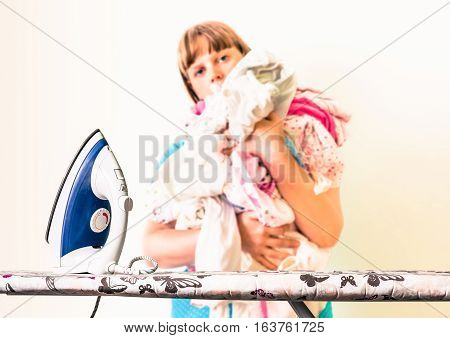 Iron on ironing board and unfocused housewife with a pile of laundry - retro style