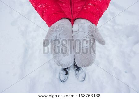 Ivory woman glove in snow with red coat
