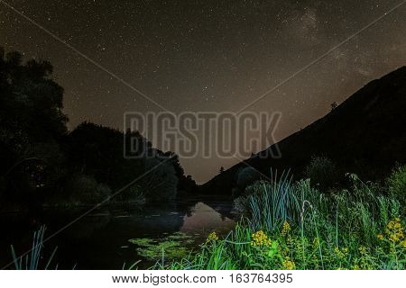 Starry night sky above the wild river in the foothills. Night natural landscape.