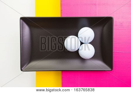Black ceramic dish with golf balls on over white yellow and pink wooden table rectangle dish