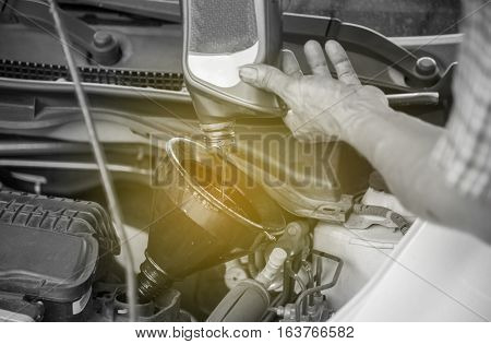 Mechanic draining engine oil from a car for an oil change at an auto shop