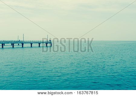 Fishing pier jutting into the blue sea and clear sky.