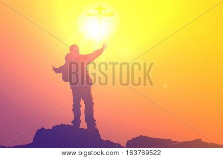 Silhouette of man praying at the top mountain with abstract  sun Cross ray