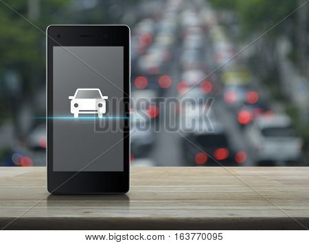 Car flat icon on modern smart phone screen on wooden table over blur of rush hour with cars and road Internet business service transportation concept