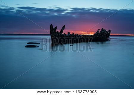 Old broken boat wreck on the shore a frozen sea and beautiful blue sunset background. Estonia Europe.