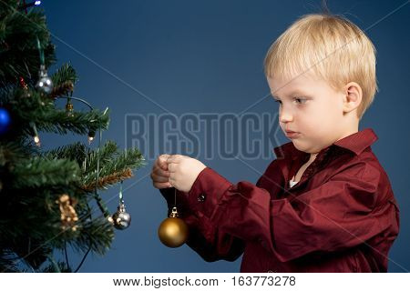 Little boy decorates the Christmas tree. Spruce with decorations. Kid and adornment.