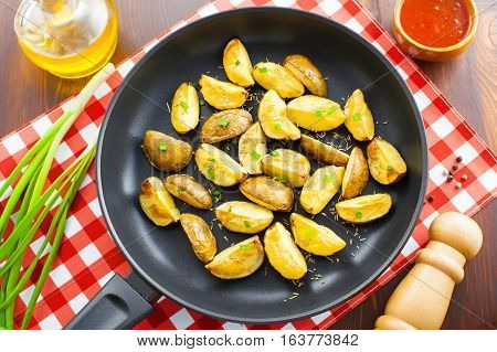 Fresh crispy potato wedges on a pan vegetarian healthy food top view