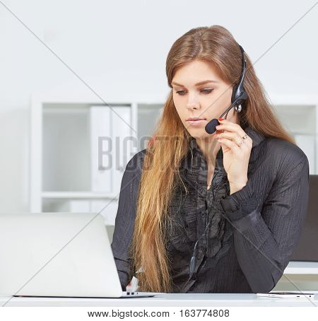 Female call center service operator at work. Portrait of pretty female helpdesk employee with headset at workplace. Effective and efficient business information help and support concept