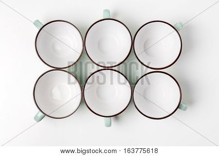 Clean dishes, coffee or tea set. Plenty of elegant empty porcelain cups at white background, high key, top view and flat lay.