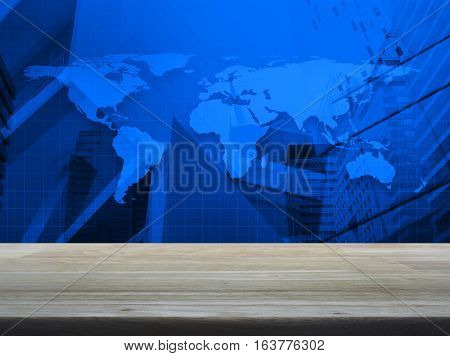 Empty brown wooden table top over world map and city tower background Elements of this image furnished by NASA