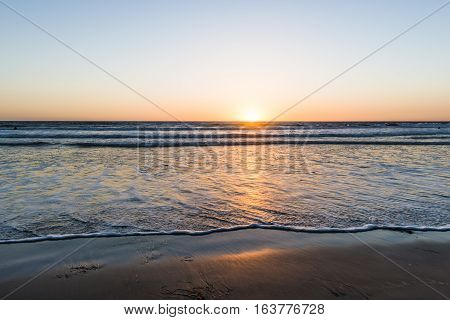 Sunset over the magnificent beach of California. Coast of Pacific ocean for an evening meditative relaxation walks.