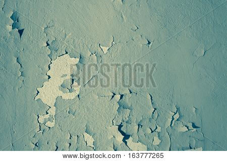 Natural background. Wall with a shabby and peeling paint and plaster. Contrast and volume. Turquoise.