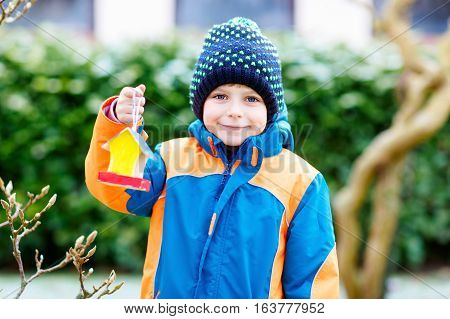 Little kid boy feeding birds in winter. Cute happy preschool child hanging colorful selfmade bird house on tree on frosty cold day. Preschooler in colorful wam clothes. Nature, empathy with animals. poster