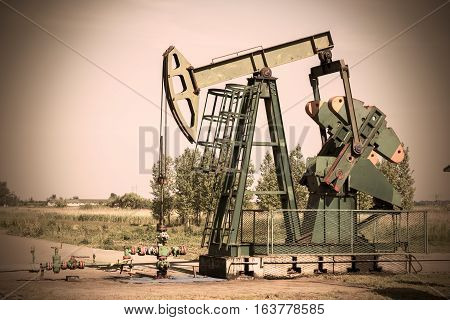 Crude oil pump in oil field. Oil and gas concept