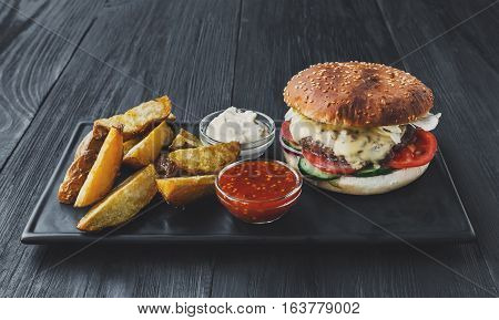 Fast food restaurant dish top view. Meat cheese burger, potato chips and wedges. Take away set on dark black wood background. Hamburger, mayonnaise and spicy tomato sauce. Filtered