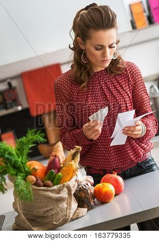 Elegant Woman Standing In Kitchen Holding Shopping List And Cash