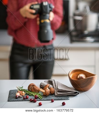 Closeup On Mushrooms Lingonberries And Rosmarinus On Table And Female Food Photographer In Backgroun