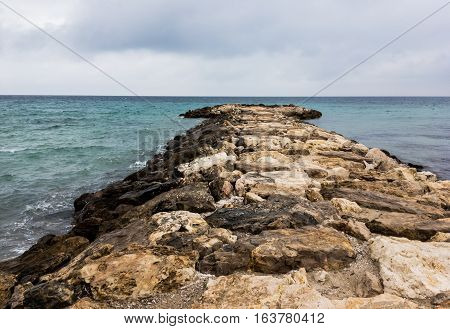 Rocky pier in early autumn cloudy weather in San Cataldo near Lecce in Italy