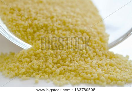 Pile of the uncooked raw cous cous near glass bowl. Healthy lifestyle concept. Closeup macro shot.